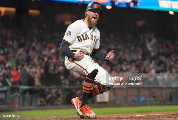 Hunter Pence of the San Francisco Giants reacts after he scored against the San Diego Padres in the bottom of the seventh inning at ATT Park on...