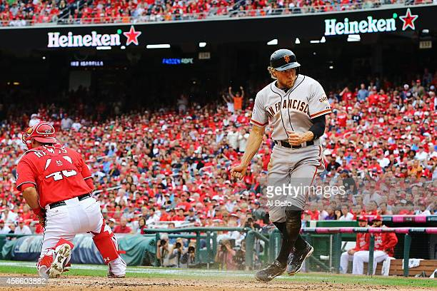 Hunter Pence of the San Francisco Giants reacts after scoring on a single by Brandon Belt in the fourth inning against the Washington Nationals...