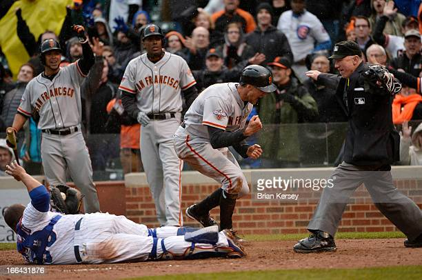 Hunter Pence of the San Francisco Giants reacts after scoring past catcher Welington Castillo of the Chicago Cubs on a double hit by Brandon Belt of...