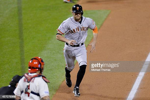 Hunter Pence of the San Francisco Giants runs home to score on an error by Matt Carpenter of the St Louis Cardinals in the second inning during Game...