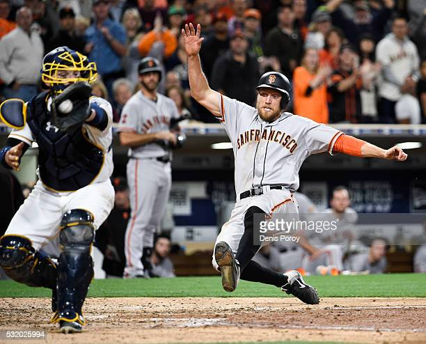 Hunter Pence of the San Francisco Giants scores as Derek Norris of the San Diego Padres fields the ball during the eighth inning of a baseball game...