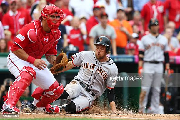 Hunter Pence of the San Francisco Giants slides home to score on a single by Brandon Belt in the fourth inning against the Washington Nationals...