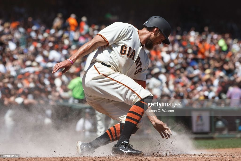 Hunter Pence #8 of the San Francisco Giants slides into home plate to score a run against the San Diego Padres during the fourth inning at AT&T Park on July 22, 2017 in San Francisco, California.