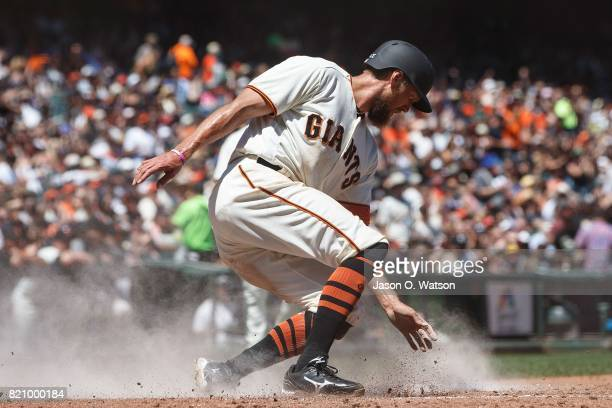 Hunter Pence of the San Francisco Giants slides into home plate to score a run against the San Diego Padres during the fourth inning at ATT Park on...