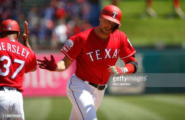 Hunter Pence of the Texas Rangers celebrates with third base coach Tony Beasley after hitting a tworun home run against the Houston Astros during the...