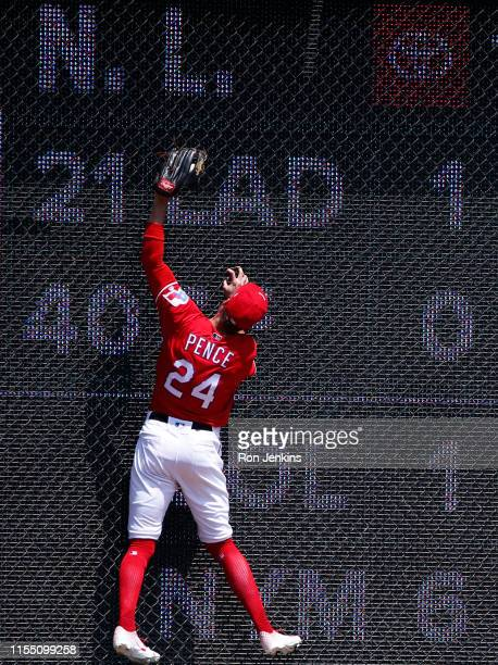 Hunter Pence of the Texas Rangers climbs the left field wall to catch a ball off the bat of Mark Canha of the Oakland Athletics during the first...