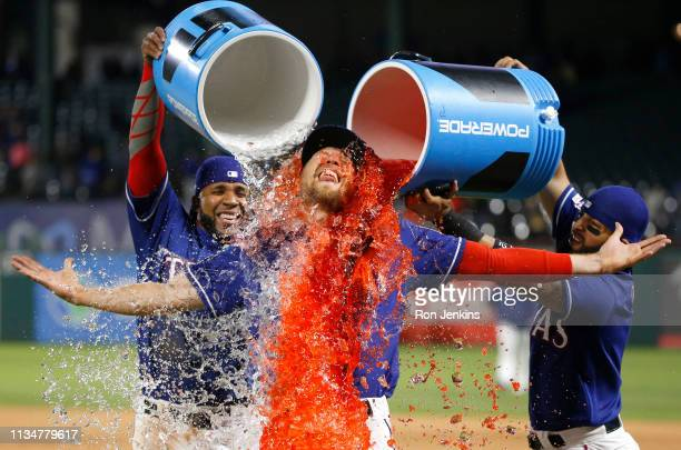 Hunter Pence of the Texas Rangers is given a Powerade bath by teammates Elvis Andrus left and Rougned Odor at Globe Life Park in Arlington on April 3...