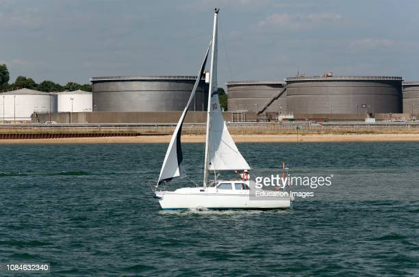 A Hunter Pilot 27 yacht with two crew passing Hamble Oil Terminal at Hamble on Southampton Water southern England UK