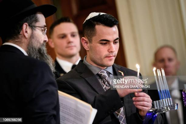 Hunter Pollack brother of Stoneman Douglas High School mass shooting victim Meadow Pollack lights a menorah during a Hanukkah reception in the East...