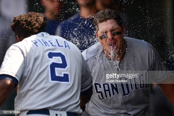 Hunter Renfroe of the San Diego Padres celebrates in the dugout as Jose Pirela splashes him in the face with water after hitting a sixth inning solo...