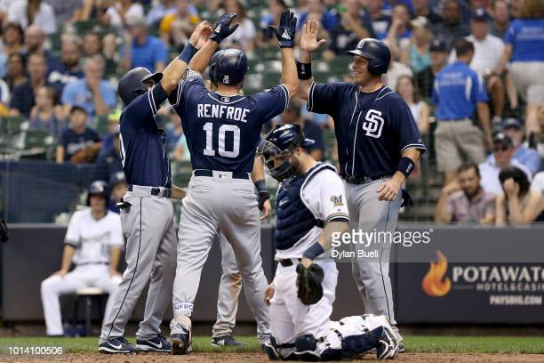 Hunter Renfroe of the San Diego Padres celebrates with teammates past Manny Pina of the Milwaukee Brewers after hitting a grand slam in the ninth...