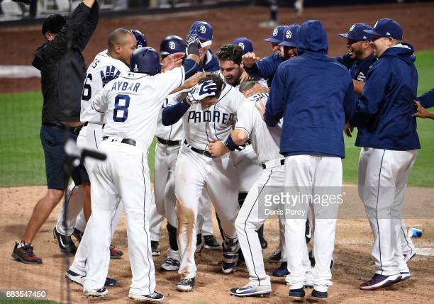 Hunter Renfroe of the San Diego Padres center is greeted at the plate by teammates after hitting a tworun walk off home run during the tenth inning...