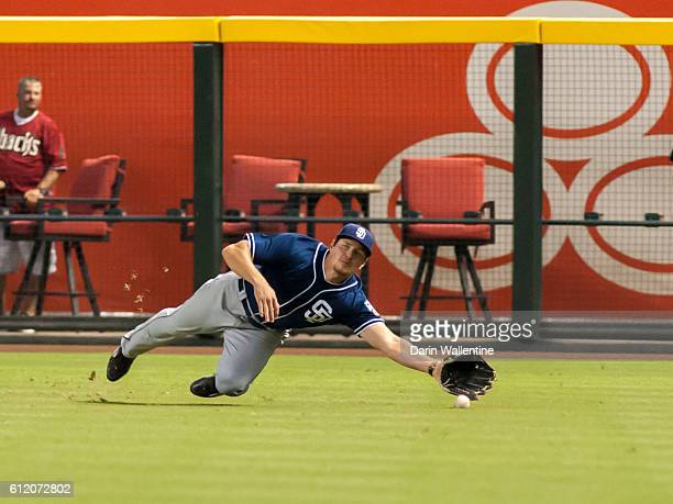 Hunter Renfroe of the San Diego Padres dives for the ball off of the bat of Mitch Haniger of the Arizona Diamondbacks in the seventh inning of the...