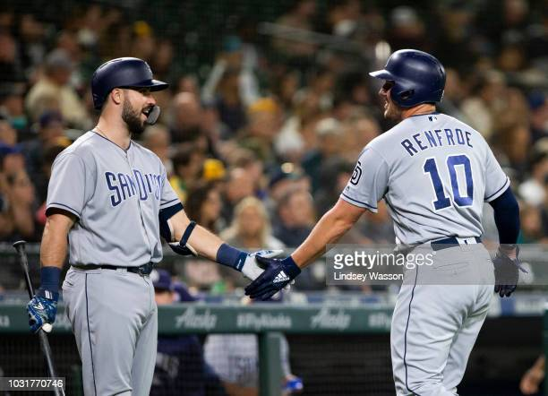 Hunter Renfroe of the San Diego Padres is greeted by Austin Hedges after scoring on a single by Franmil Reyes against the Seattle Mariners in the...