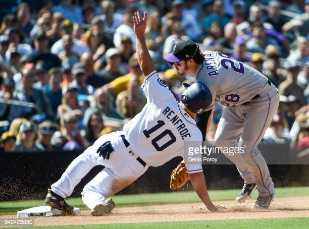 Hunter Renfroe of the San Diego Padres is tagged out at third base by Nolan Arenado of the Colorado Rockies during the seventh inning of a baseball...