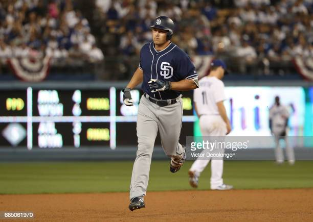 Hunter Renfroe of the San Diego Padres jogs to third base after hitting a solo homerun as Logan Forsythe of the Los Angeles Dodgers looks on in the...