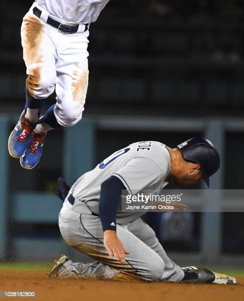Hunter Renfroe of the San Diego Padres steals second as Chris Taylor of the Los Angeles Dodgers leaps for the throw in the fourth inning at Dodger...