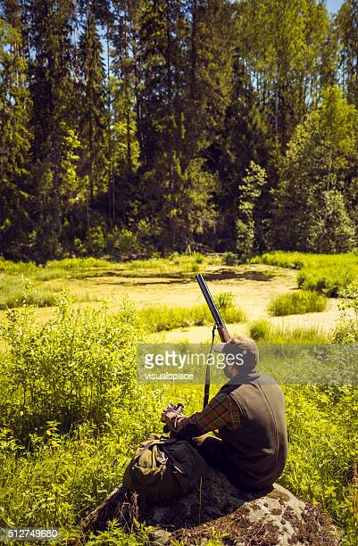 Hunter Resting In A Swamp Field