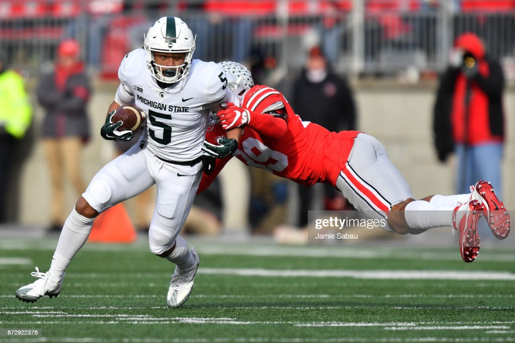 Hunter Rison #5 of the Michigan State Spartans shakes off the tackle from Malik Harrison #39 of the Ohio State Buckeyes in the fourth quarter to pick up yardage at Ohio Stadium on November 11, 2017 in Columbus, Ohio. Ohio State defeated Michigan State 48-3.