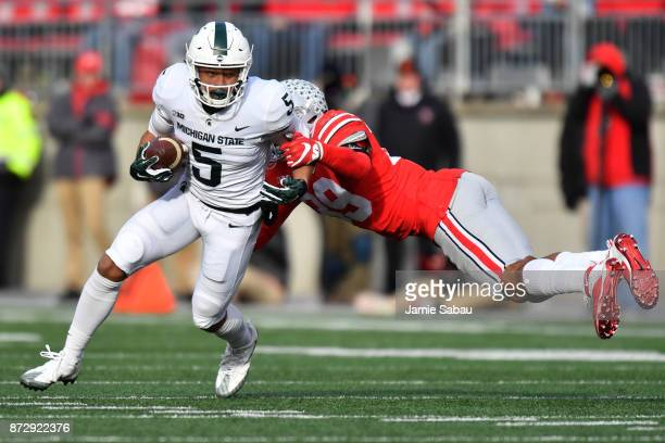 Hunter Rison of the Michigan State Spartans shakes off the tackle from Malik Harrison of the Ohio State Buckeyes in the fourth quarter to pick up...