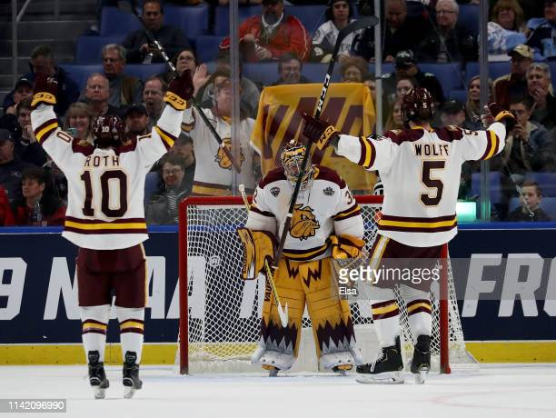 Hunter Shepard of the MinnesotaDuluth Bulldogs celebrates the 41 win over the Providence Friars with teammates Kobe Roth and Nick Wolff during the...