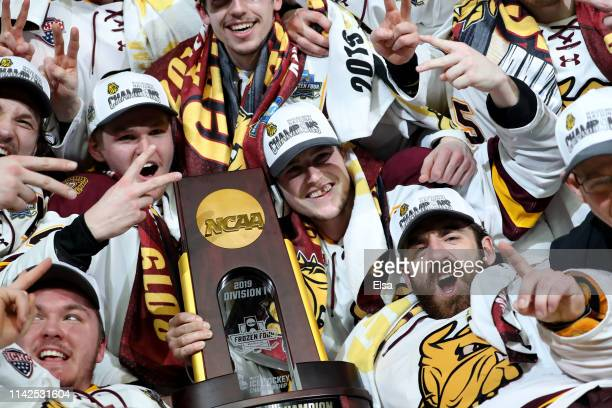 Hunter Shepard,Parker Mackay and the rest of the Minnesota-Duluth Bulldogs celebrate with the trophy after the 2019 NCAA Frozen Four the championship...