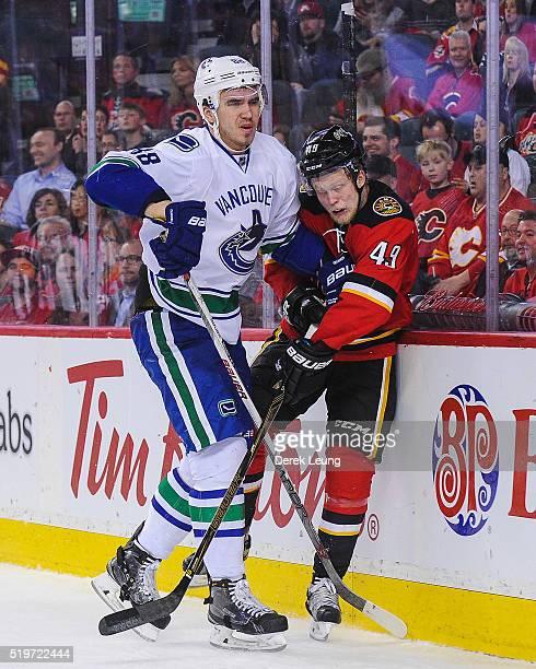 Hunter Shinkaruk of the Calgary Flames is checked by Nikita Tryamkin of the Vancouver Canucks during an NHL game at Scotiabank Saddledome on April 7...