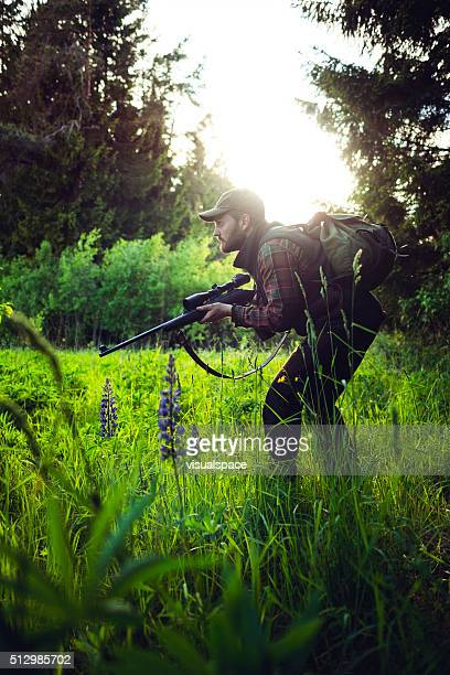 Hunter Sneaking With A Shotgun in a Sunlit Green Forest