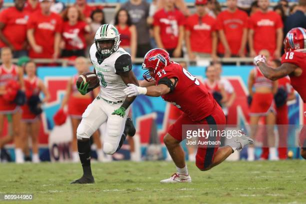 Hunter Snyder of the Florida Atlantic Owls pursue Tyler King of the Marshall Thundering Herd as he runs with the ball at FAU Stadium on November 3...
