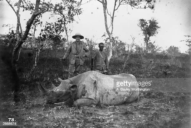 A hunter standing over a dead rhinoceros