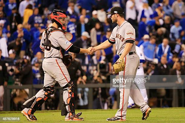 Hunter Strickland of the San Francisco Giants celebrates with Buster Posey after defeating the Kansas City Royals by a score of 71 to win Game One of...