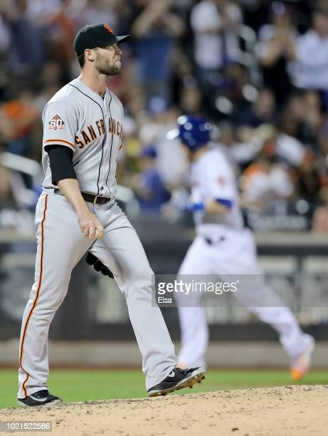 Hunter Strickland of the San Francisco Giants reacts as Todd Frazier of the New York Mets rounds third base after he hit a solo home run in the...