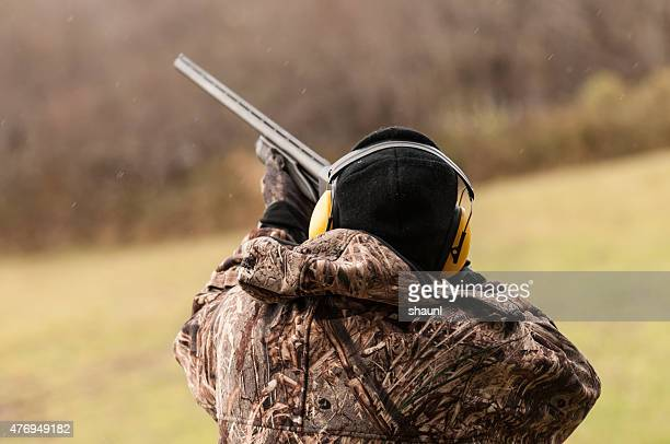 hunter takes aim at target - clay pigeon shooting stock pictures, royalty-free photos & images