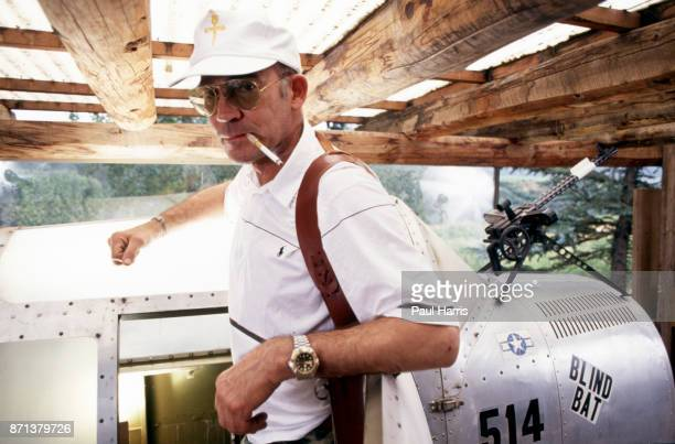 Hunter Thompson aka Hunter S Thompson aka Gonzo Journalist at his ranch standing next to his Link Trainer with a pistol on October 12 1990 in Woody...