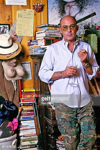 Hunter Thompson aka Hunter S Thompson aka Gonzo Journalist at his ranch standing against a bookcase with a Ralph Steadman picture on the wall on...