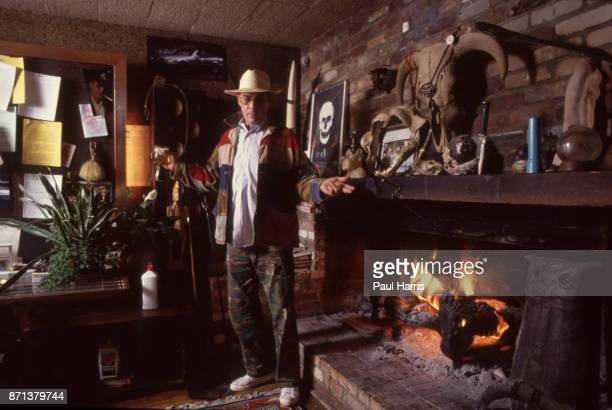 Hunter Thompson aka Hunter S Thompson aka Gonzo Journalist at his ranch standing next to his fireplace after adding logs to burn on October 12 1990...