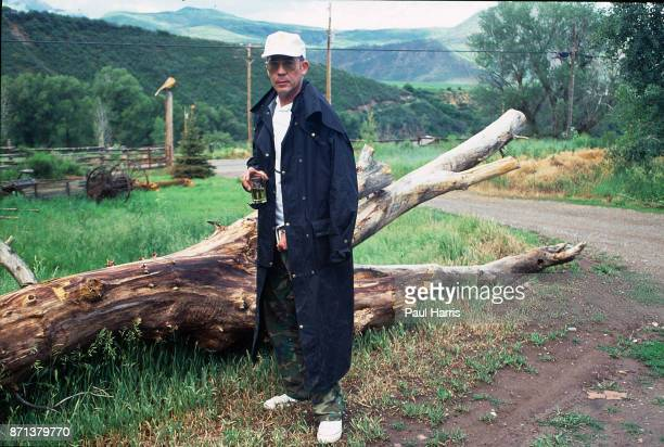 Hunter Thompson aka Hunter S Thompson aka Gonzo Journalist at his ranch standing next to a fallen tree whilst drinking a whisky and smoking on...