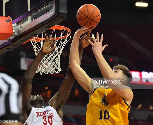 Hunter Thompson of the Wyoming Cowboys shoots against Jonathan Tchamwa Tchatchoua of the UNLV Rebels during their game at the Thomas Mack Center on...