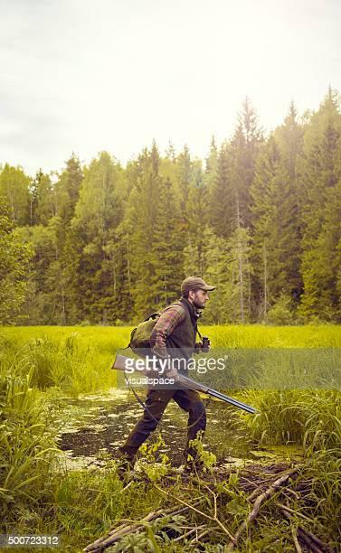 Hunter Travelling Over Swamp Near Forrest