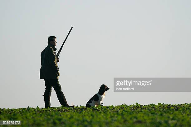 A hunter waits with his dog for pheasants to shoot during a pheasant shoot near Sherbourne Warwickshire England The pheasant shooting season in...