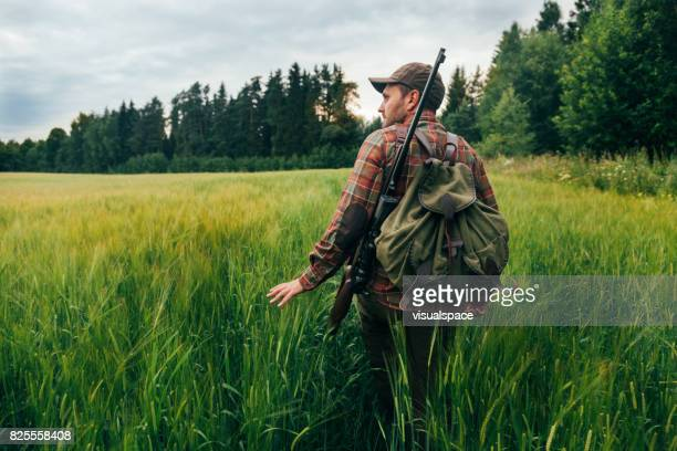 hunter walking on a field - hunting sport stock pictures, royalty-free photos & images