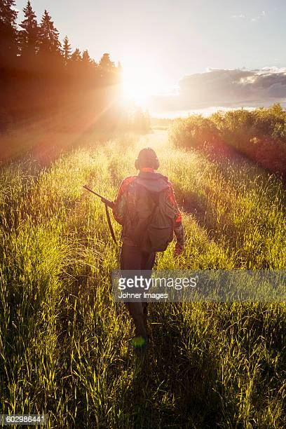 hunter walking through meadow - hunting sport stock pictures, royalty-free photos & images