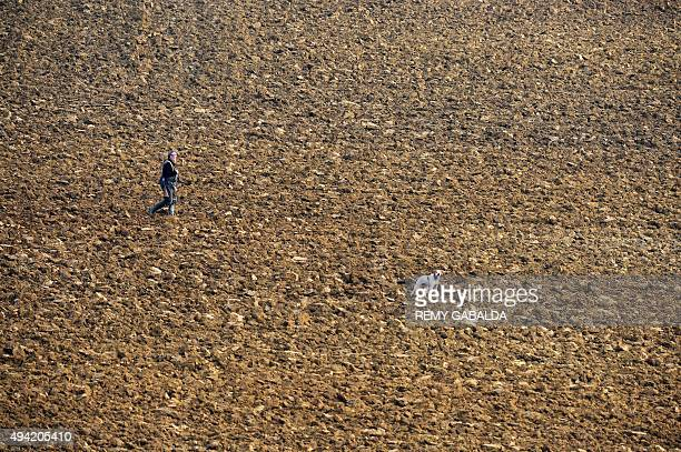 A hunter walks with his dog through a field near Toulouse on October 25 2015 AFP/ REMY GABALDA