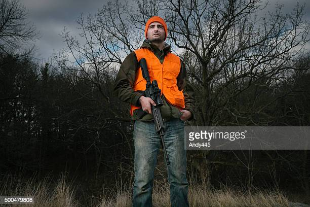 hunter with a rifle - hoofddeksel stockfoto's en -beelden