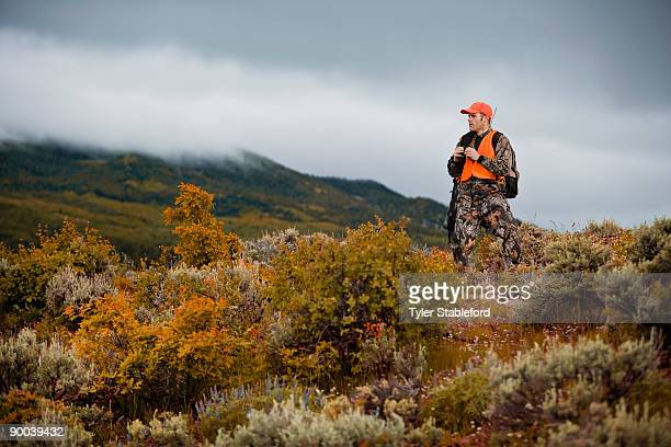 hunter with binoculars and rifle looking out.  - 狩人 ストックフォトと画像
