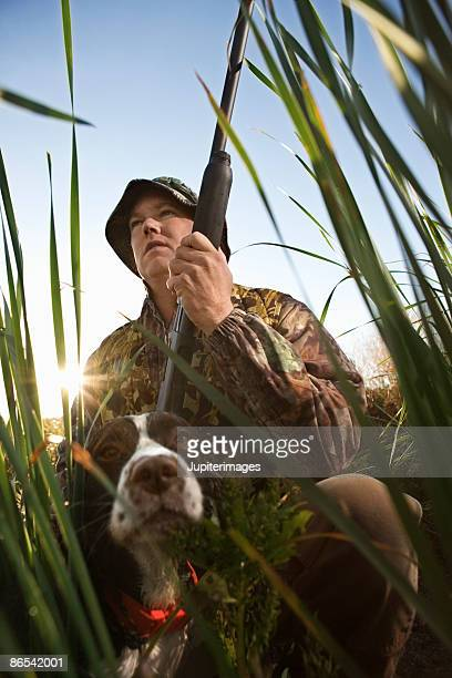 Hunter with dog and rifle in reeds