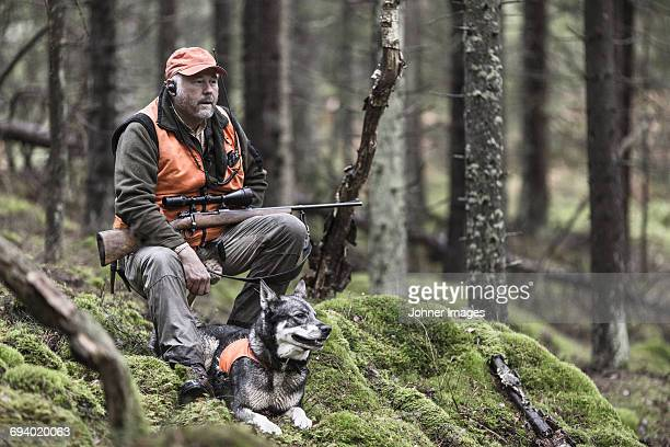 Hunter with dog in forest