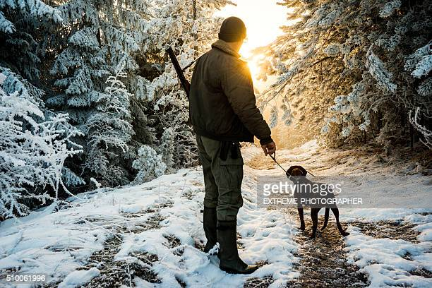 hunter with dog in the snowy forest - hunting dog stock pictures, royalty-free photos & images