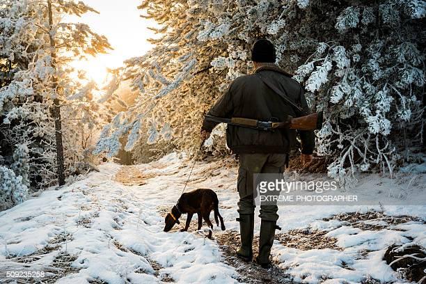 Jäger mit Hund an der Leine geführt