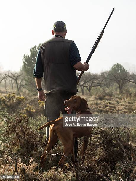 Hunter with his weapon and hunting dog in the mount